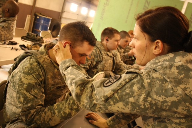 Capt Jennifer Noetzel, Chief Audiologist, USA MEDDAC, Fort Drum, NY assist a Soldier assigned to Company Alpha, First Battalion, 87th Infantry Regiment to properly insert the TCAPS/Tactical Communication And Protection system during a weeklong familiarization and training session on Fort Drum.