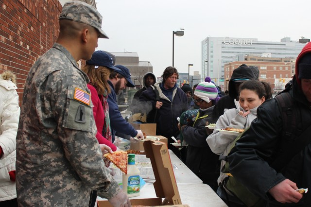Sgt. Richard Saenz, an observer-coach/trainer with 2-312th Regiment, 174th Infantry Brigade, Division East, First Army, volunteers during his off-duty time to serve pizza to homeless people in Camden, N.J., March 2, 2014. Saenz, originally from Camden, collected donations from 2-312th Soldiers to purchase the pies. Saenz said seeing a friend helping those in need motivated him to find ways he can give back and make a difference.