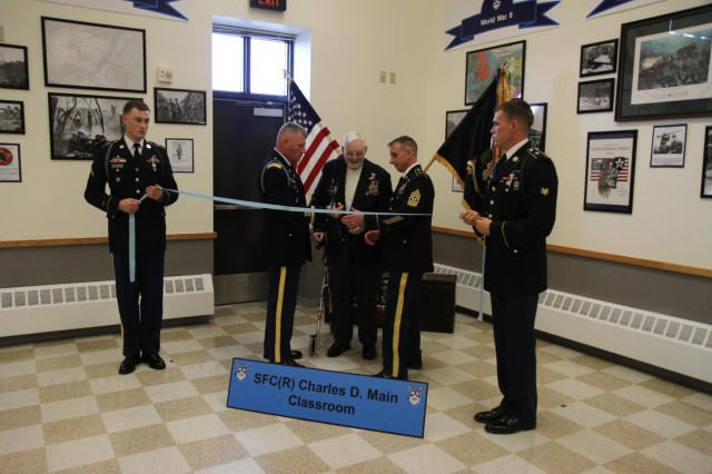 Sgt. 1st Class Charles Main (center), retired, cuts a blue ribbon with a ceremonial tomahawk to officially dedicate the room named in his honor during a ceremony March 7. Main is the honorary command sergeant major of the 23rd Infantry Regiment.