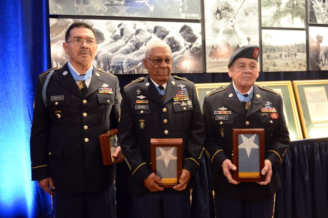Vietnam War veterans and Medal of Honor recipients (left to right) former Sgt. Santiago Erevia, retired Sgt. 1st Class Melvin Morris, and retired Master Sgt. Jose Rodela, hold their encased Medal of Honor flags, presented to them at the Pentagon, March 19, 2014, one day after they received the nation's highest award for valor.
