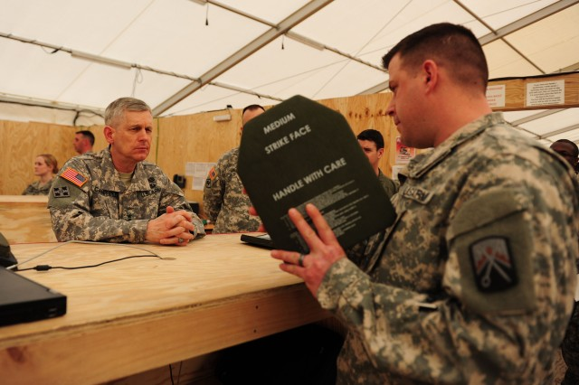Lt. Gen. Donald Campbell, commander of U.S. Army Europe, is shown the procedures to test body-armor plates by a Soldier assigned to Sustainment Task Force-16, 21st Theater Sustainment Command, during his visit here, March 19. During his visit, Campbell was shown how base operations and procedures function while also meeting Soldiers and Airmen who are currently stationed here. The MK Air Base Passenger Transit Center, which officially began running at full capacity March 1, is designed to move U.S. service members into and out of the Operation Enduring Freedom theater. The center is replacing the U.S. transit facility at Manas Air Base in Kyrgyzstan as the contract between the U.S. and Kyrgyzstan ends this summer. The Romanian air base has been operational, and the 21st has engaged in multi-modal transportation support there, for many years. But it was not configured to support the new transit center mission, which requires moving the thousands of troops and thousands of tons of cargo and supplies that accompanies the drawdown in Afghanistan.