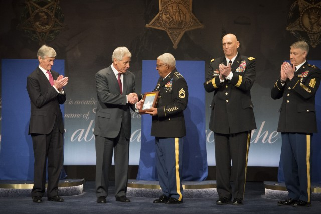 Secretary of Defense Chuck Hagel, accompanied by U.S. Army leadership, presents the Medal of Honor flag to Sgt. 1st Class (Ret.) Melvin Morris during the Pentagon's Hall of Heroes Induction Ceremony, in the Pentagon in Arlington, Va., March 19, 2014. Morris was one of 24 Medal of Honor recipients recognized at the induction ceremony.