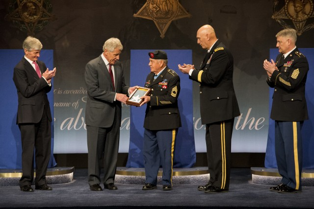 Secretary of Defense Chuck Hagel, accompanied by U.S. Army leadership, presents the Medal of Honor flag to Medal of Honor recipient Master Sgt. (Ret.) Jose Rodela during the Pentagon's Hall of Heroes Induction Ceremony, in the Pentagon in Arlington, Va., March 19, 2014. Rodela was one of 24 Medal of Honor recipients recognized at the induction ceremony.