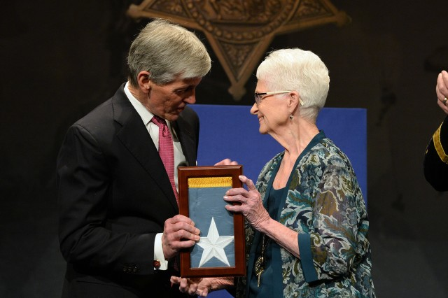 Secretary of Army John McHugh presents the Medal of Honor Flag to Nancy Weinstein, on behalf of her husband, Sgt. Jack Weinstein, one of 24 Army veterans honored during the Valor 24 Hall of Heroes Induction ceremony, held at the Pentagon, Arlington, Va, March 19, 2014. (U.S. Army photo by Mr. Leroy Council/Released)
