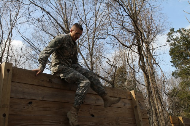 Spc. Curtis Anderson, a competitor assigned to the 95th Regiment, 3rd Brigade, 100th Training Division, climbs over the wall obstacle wraps the rope around his foot to help with reaching the top of rope-climb obstacle during the 80th Training Command Best Warrior Competition obstacle course at Fort Knox, Ky., March 19, 2014.