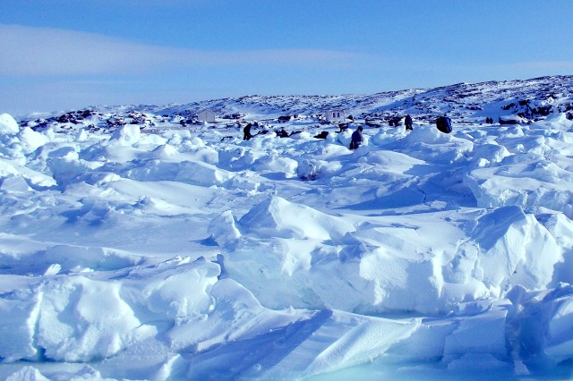Large chunks of ice forged by the sea surround a bivouac area where Soldiers break camp and prepare to move out.