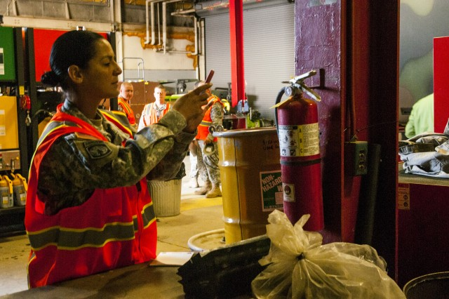 Staff Sgt. Sandra E. Rivera, Interior Electrician instructor, 5th Brigade, 94th Training Division, photographs the tag on an expired fire extinguisher identifying it as a safety hazard at a maintenance facility, Fort Knox, Ky. March 20, 2014. Rivera and 48 other Citizen-Soldiers participated in an Army Safety and Composite Risk Management Course conducted by the 80th Training Command safety office in conjunction with the U.S. Army Combat Readiness/Safety Center. The students were tasked with finding and photographing safety violations in and around the facility, which they used during a class presentation.