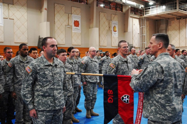 "On Camp Casey March 5, Maj. Gen. Thomas S. Vandal (right), Commanding General, 2nd Infantry Division, places a streamer for ""Excellence in Resiliency"" on guidon of the division's Company C, Headquarters and Headquarters Battalion, one of three first-place winners of the coveted 2013 Area I Commander's Cup award. In foreground near Vandal are the company's commanding officer, Capt. Sean Hayes (left), and 1st Sgt. David Reickmann. A new scoring system for the Area I Cup calls for participation not only in sports but in a variety of other resilience-building activities. Other first place winners were 61st Chemical Company, 23rd Chemical Battalion, and Company D, 1st Battalion, 72nd Armor Regiment. "" U.S. Army photo by Pfc. Noh Ha-kyung"