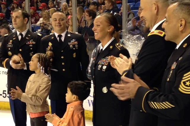 Sgt. Kara Wilson (center) was named Tobyhanna Army Depot's Warfighter of the Quarter during a ceremony at a Wilkes-Barre/Scranton Penguins hockey game Feb. 22. During the event, she was joined by (from left) Capt. Jeremy Glosson, 1st Sgt. Douglas Hawkins, her husband and children, and depot commander Col. Gerhard P.R. Schröter and Sgt. Maj. Juan Rocha.