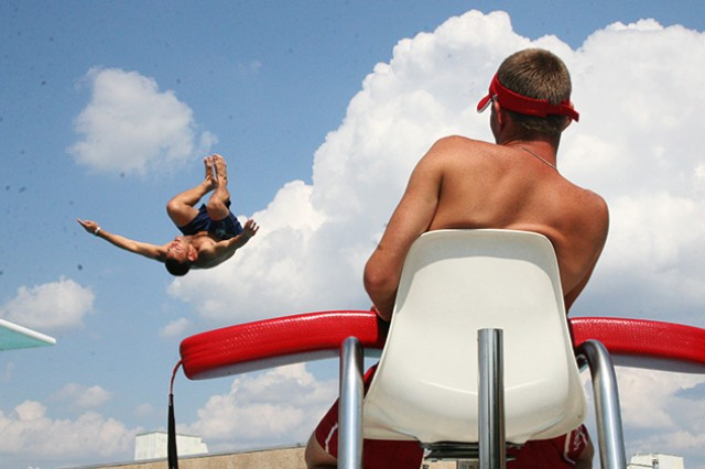 A lifeguard at a Fort Rucker facility watches a swimmer dive for the water during a previous swim season.