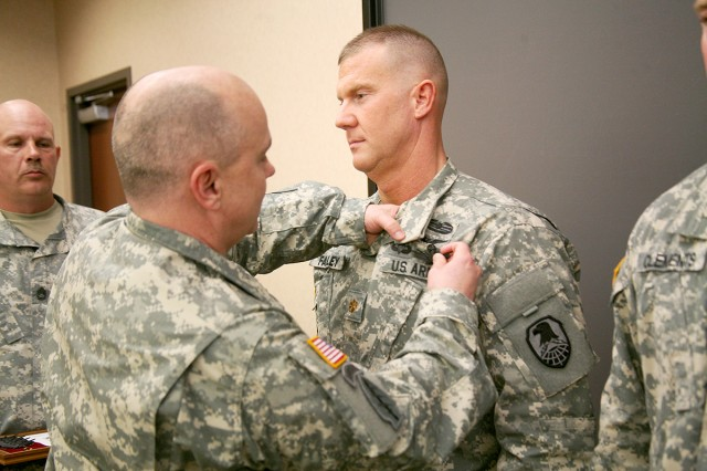 Col. Tom James, deputy director, Future Warfare Center, U.S. Army Space and Missile Defense Command/Army Forces Strategic Command, presents Maj. Christopher Fairley the Master Army Space Badge during a ceremony at the command�'s Redstone Arsenal, Ala., headquarters March 19.