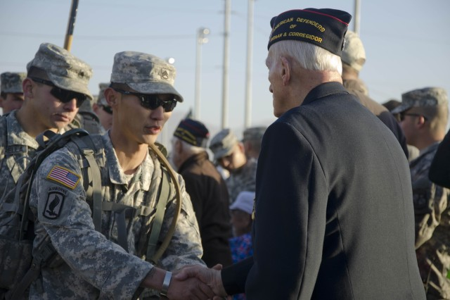 "A Soldier shakes the hand of Bataan POW William ""Lyle"" Eldridge before beginning the march."