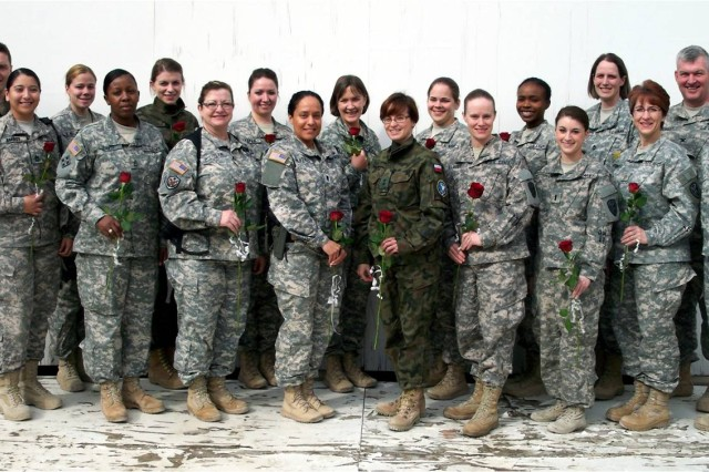 Female soldiers with the Kosovo Force's Multinational Battle Group-East pose for a group photo with the roses they received on International Women's Day at Camp Bondsteel, Kosovo, March 8. MNBG-E commander, Col. Charles Hensley (second from right) and Command Sgt. Maj. Bernardo B. Serna (far right) join in on the picture.