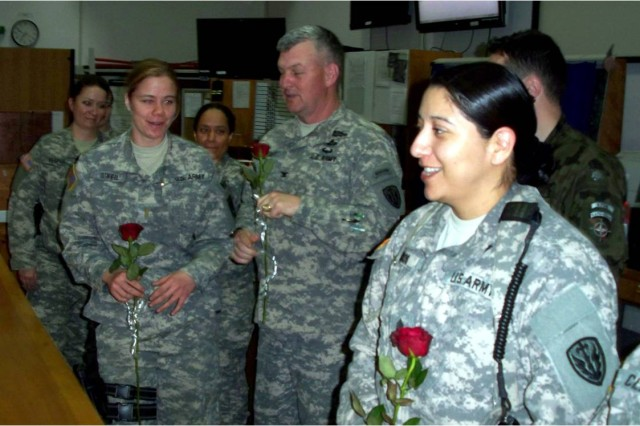 U.S. Army 2nd Lt. Julia O'Neil receives a rose from Col. Chuck Hensley, commander of Multinational Battle Group-East, in recognition of the women's importance in the armed forces worldwide, during a ceremony at Camp Bondsteel, Kosovo, March 8.