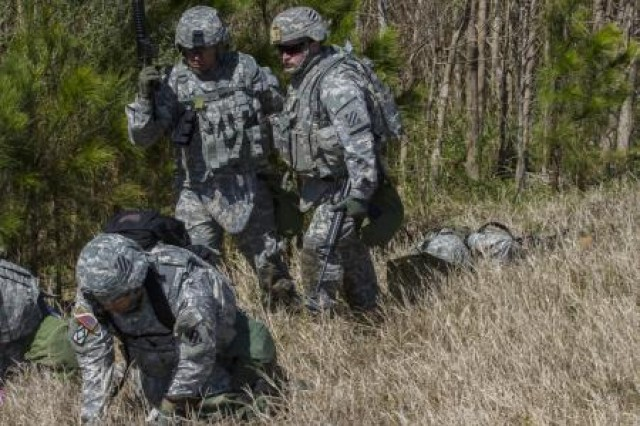 The 3rd Squadron, 17th Cavalry Regiment Spur Ride candidates drag the body of their fallen comrade while another searches for mines during the Lighthorse Spur Ride on Hunter Army Airfield March 13. The Spur Ride candidates covered a distance of over 20 miles in less than two days.