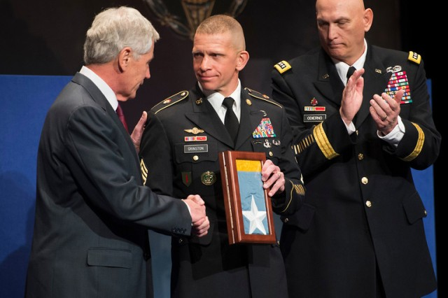 Command Sgt. Maj. Michael A. Grinston, 1st Inf. Div. senior enlisted leader, accepts the Medal of Honor flag from Secretary of the Army John McHugh during the Hall of Heroes Induction Ceremony at the Pentagon in Arlington, Va., March 19. Twenty-four Medal of Honor recipients were inducted, spanning from three conflicts: Vietnam War, Korean War and World War II. Grinston accepted the flag on behalf of the family of the 1st Inf. Div.'s Sgt. Candelario Garcia. (U.S. Army photo by Staff Sgt. Bernardo Fuller)
