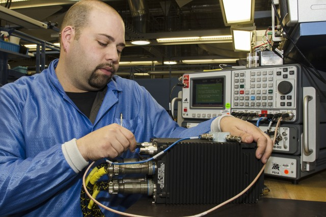 Electronics Mechanic Brett Bellas connects an AN/ARC-231 radio to an automated test set for final testing at Tobyhanna Army Depot.