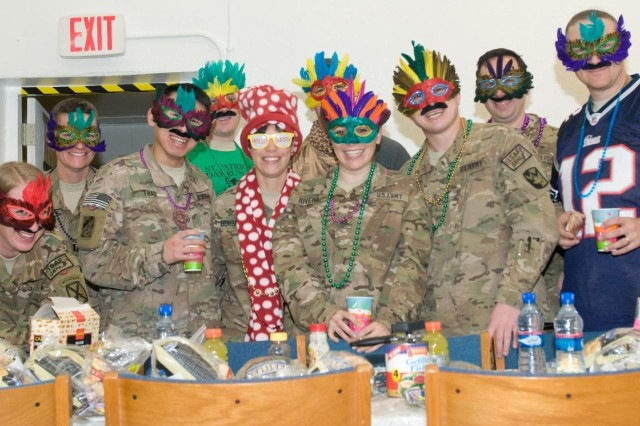 Attendees partake in food and fellowship after a service at Bagram Air Field, Afghanistan, on March 15, 2014. Dressing up is a tradition of Purim, the most joyous of Jewish holidays. (U.S. Army photo by Sgt. Jarred Woods, 1st Sustainment Command (Theater).)
