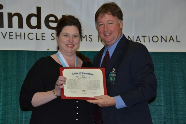 Dana Osborne, left, operations chief for Unmanned Aircraft Systems, accepts the certificate from Peter Blocker, AUVSI chapter president, inducting her into the Order of Prometheus during the Association for Unmanned Vehicle Systems International Pathfinder symposium March 19 at the Von Braun Center in Huntsville, Ala.