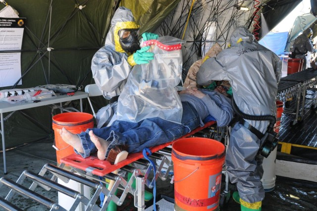 Soldiers with the 44th Chemical Company, 2nd Chemical Battalion, 48th Chemical Brigade, collects the personal belongings of a civilian role player prior to decontamination procedures March 17, 2014, during a field training exercise. U.S. Army North Command oversaw the exercise by severing as the facilitators and observers as part of the Defense CBRNE (Chemical, Biological, Radiological, Nuclear and Explosive) Reactionary Force (DCRF) mission.