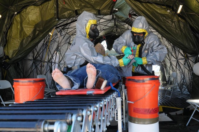 Soldiers with the 44th Chemical Company, 2nd Chemical Battalion, 48th Chemical Brigade, removes the contaminated clothes of a civilian role player during a field exercise March 17, 2014. The unit participated in a mass casualty decontamination exercise validation.