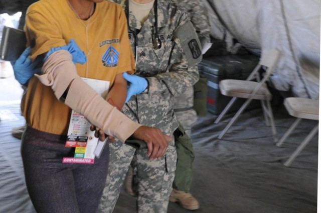 """Sgt. Leticia Balderao, a combat medic with the 566th Area Support Medical Company, 61st Multifunctional Medical Battalion, 1st Medical Brigade, and a Whittier, Calif., native, helps an """"ambulatory patient"""" during a mass decontamination field exercise March 19, 2014, in preparation for the upcoming Defense CBRNE (Chemical, Biological, Radiological, Nuclear and Explosive) Reactionary Force mission. An ambulatory status means the patient can walk."""