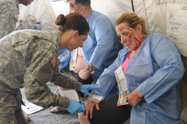A Soldier with the 566th Area Support Medical Company, 61st Multifunctional Medical Battalion, 1st Medical Brigade, assists a civilian role player wearing moulage makeup during a field training exercise March 19, 2014. Moulage is makeup used to create realistic injuries for the purpose of training medical personnel.