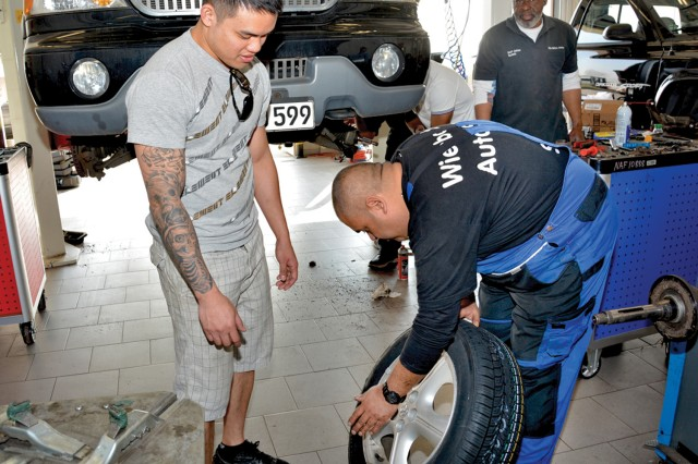 "The Wiesbaden Auto Skills Center's ""Big John"" Cobb (right) assists American Forces Network Wiesbaden's Sgt. Jedhel Somera with mounting and balancing a set of new tires."