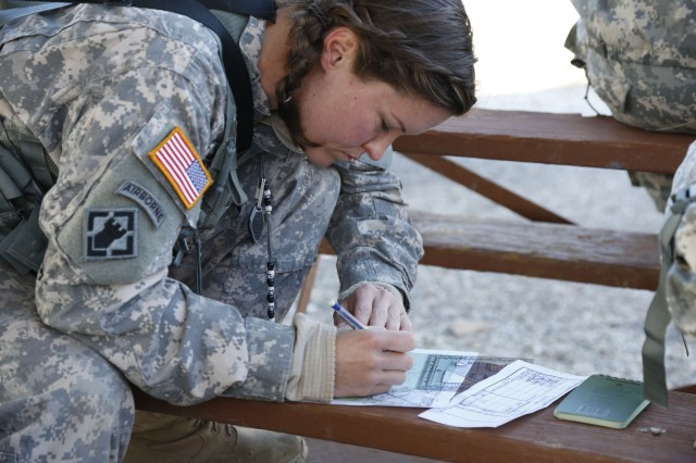 Staff Sgt. (Kathleen) Amy Justice, a competitor assigned to the 7/95th Regiment, 4th Brigade, 94th Training Division, plots points to begin the land navigation course during the Best Warrior Competition at Fort Knox, Ky., Mar. 20, 2014. (U.S. Army photo by Pfc. Jamill Ford/Released)