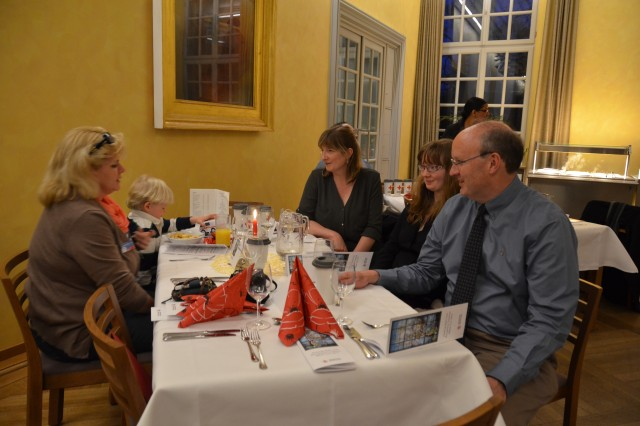 Attendees at an American Red Cross volunteer recognition ceremony talk over dinner following the ceremony in downtown Ansbach March 21, 2014.