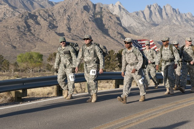 Three members of U.S. Army South's 1st Battlefield Coordination Detachment lead the pack as they march along the highway during the 25th Bataan Memorial Death March at White Sands Missile Range, N.M. March 23.