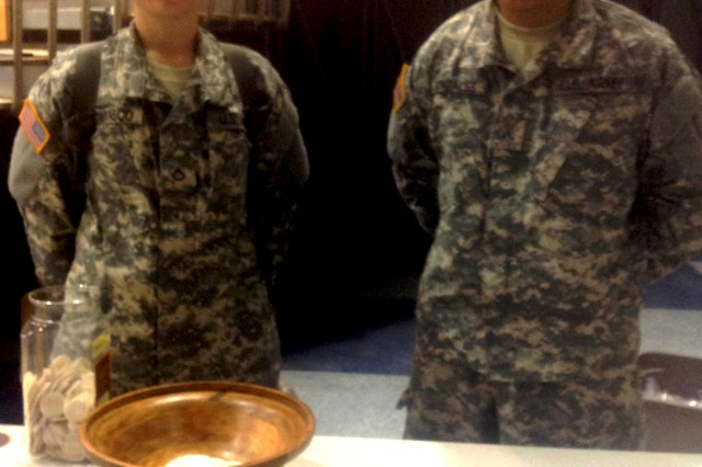 Pvts. Angela Carrasco and Pierre Gonzalez receive a prayer packet during Sunday Mass for Basic Combat Training Soldiers at Fort Jackson, S.C.