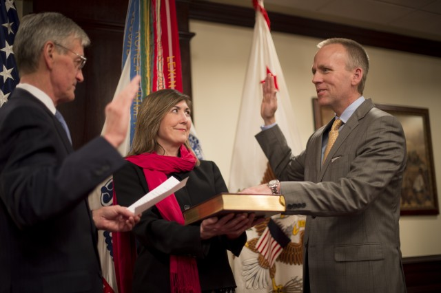 Secretary of the Army John McHugh administers the oath of office to Brad R. Carson to be the 31st Under Secretary of the Army, as his wife, Julie, holds the Bible, during a ceremony at the Pentagon, March 27, 2014. Carson previously served as the Army's 20th General Counsel, a position held since 2012.