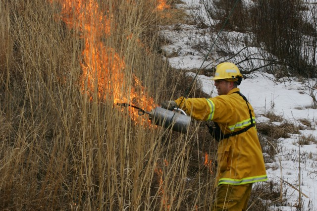 Fort McCoy Firefighter Brady Brever ignites a section of brush during a prescribed burn on South Post of Fort McCoy, Wis.