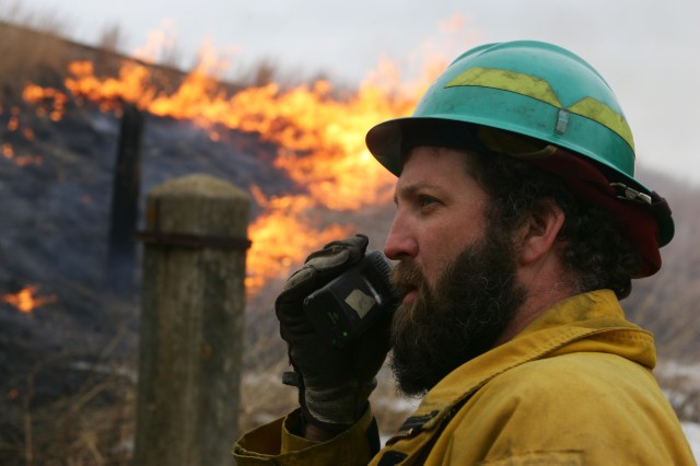 Charles Mentzel, Fort McCoy, Wis., forestry technician, communicates over the radio while overseeing a prescribed burn.