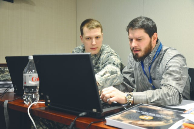 """Two students discuss proposed solutions to a simulated cyber defense challenge while participating in the Cyber - Digital Master Gunner Solution Course """"capstone challenge,"""" at Fort Belvoir, Va., March 21, 2014."""