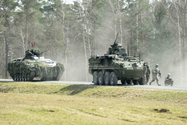 ROSE BARRACKS, Germany -- U.S. Army Stryker vehicle (right) and a German army tank stop to offload Troopers with 2nd Squadron, 2d Cavalry Regiment and German Army soldiers with Panzergrenadierbataillon 122 during a training exercise March 27, 2014, at Grafenwoehr Training Area, Germany. Troopers with the Regiment and German army conducted live-fire training to sustain their combat readiness and further their historical partnership in Europe.