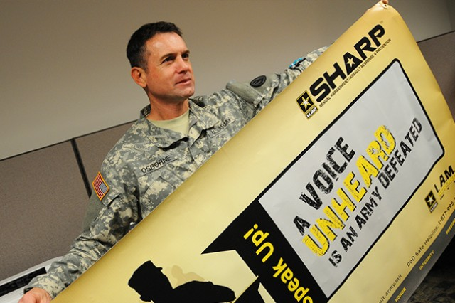 Sgt. 1st Class Lance Osborne, U.S. Army Aviation Center of Excellence and Fort Rucker, Ala., Sexual Harassment/Assault Prevention and Response Program manager, holds up a SHARP banner, March 19, 2014.