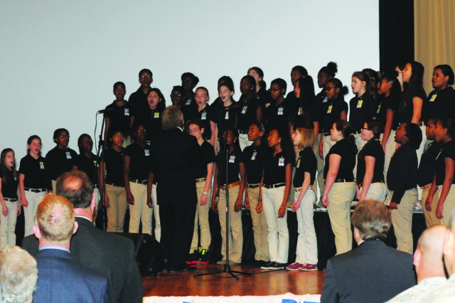 "The Vernon Middle School Choir, directed by Gene Davis, performs for 700 plus educators, Fort Polk officials and parents during the first Fort Polk Education Symposium, part of an initiative where community stakeholders collaborate to help improve Vernon Parish education. The choir sang ""The Star Spangled Banner,"" and ""God Bless America."""