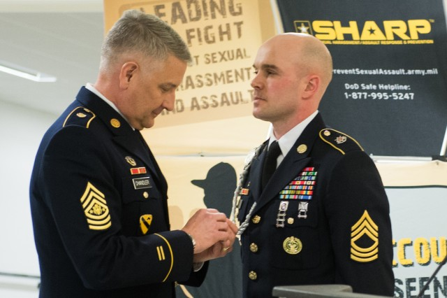 Sgt. Maj. of the Army Raymond F. Chandler III awards the Meritorious Service Medal to Master Sgt. Richard Fry for being selected as the Army's 2014 Sexual Assault Response Coordinator of the Year. The presentation was made at a Pentagon ceremony that marked the beginning of Sexual Assault Awareness Month.