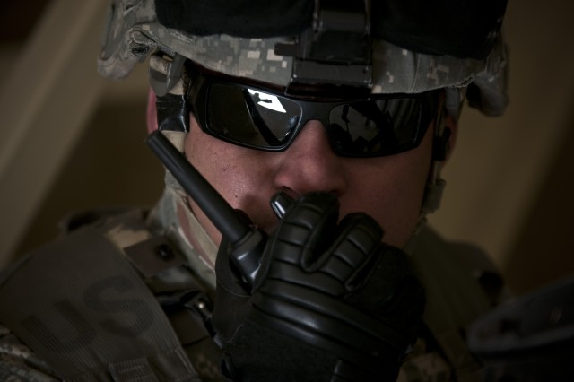 "Army Reserve Sgt. John Aventuna, a competitor in the 302nd Maneuver Enhancement Brigade's Best Warrior Competition, uses a walkie-talkie to simulate calling his higher headquarters during the event's tactical ""mystery event"" March 24, 2014, at Fort Devens"