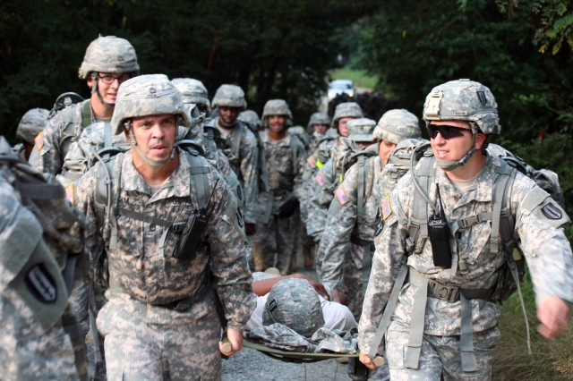 Capt. Michael A. Chezum and Sgt. 1st Class Jeremy R. Holm helped carry the litter on the tactical ruck march that Charlie Company used to get to the training area during a Field Training Exercise at the Camp Humphrey Training Area, in South Korea.