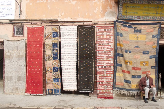A shop owner displays rugs for sale.