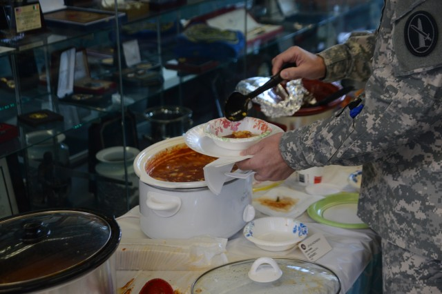 A U.S. Army Military District of Washington Soldier tries a bowl of chili during the Joint Force Headquarters-National Capital Region/U.S. Army Military District of Washington Chili Cook-Off fundraiser at Fort Lesley J. McNair, March 26, 2014.