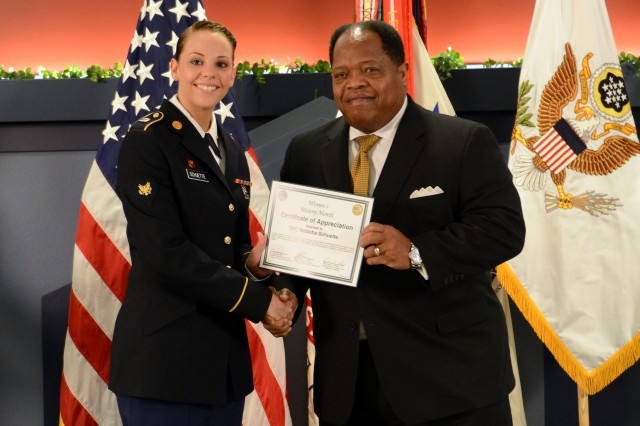 Sexual Assault Prevention advocate Spc. Natasha Schuette receives a certificate of appreciation presented by Clarence Johnson, the Department of Defense's director of the Office of Diversity Management and Equal Opportunity, at the Pentagon, March 31, 2014.