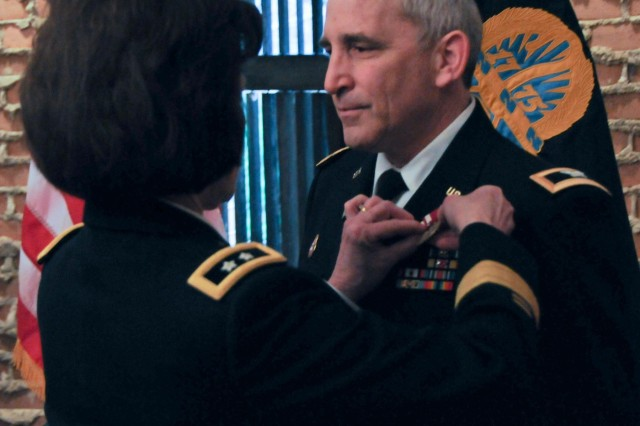 Col. Mark Sachs, command chaplain of the Army Reserve's 99th Regional Support Command, right, receives the Meritorious Service Medal from Maj. Gen. Margaret W. Boor, 99th RSC commanding general, during Sachs' retirement ceremony March 7 at the Fort Magruder Hotel and Conference Center in Williamsburg, Va.