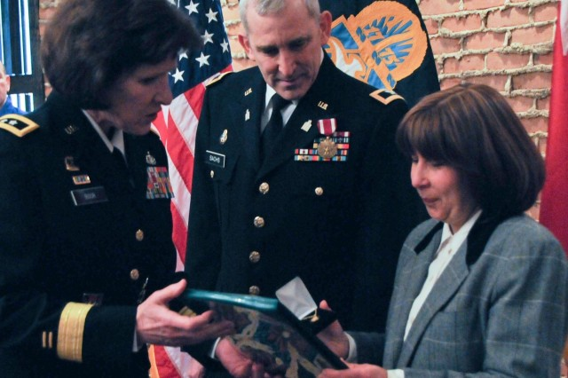 Maj. Gen. Margaret W. Boor, commanding general of the Army Reserve's 99th Regional Support Command, left, presents a certificate of appreciation and pin to Sara Sachs, right, during the March 7 retirement ceremony for Col. Mark Sachs, 99th RSC command chaplain, center, at the Fort Magruder Hotel and Conference Center in Williamsburg, Va.