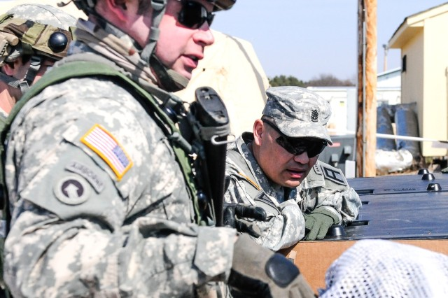 Command Sgt. Maj. Patrick K. Akuna, center, Division West command sergeant major, views laundry operations with Staff Sgt. Jordan Willsey, a noncommissioned officer with the Army Reserve's 855th Quartermaster Company from Southbend, Ind., on Forward Operating Base Freedom at Ft. McCoy, Wis., during the Warrior Exercise (WAREX) 86-14-02, Mar. 30.