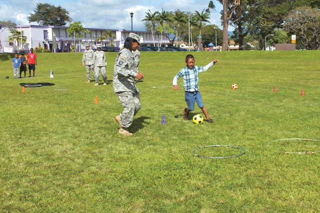 """A Soldier cheers on a keiki as he makes his way through the """"Diploma Dash"""" obstacle course during Island Palm Communities' Live & Learn 101 Festival, held at the Kaena Community Center, March 19."""