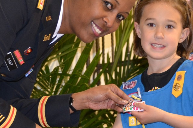 ALBUQUERQUE, N.M., -- District Commander Lt. Col. Gant presents one of the Girl Scouts with her Owl Prowl badge, March 22, 2014.
